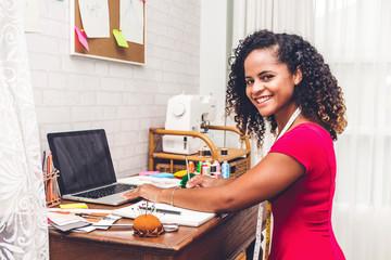Smiling african american black woman fashion designer working with laptop computer at workshop studio
