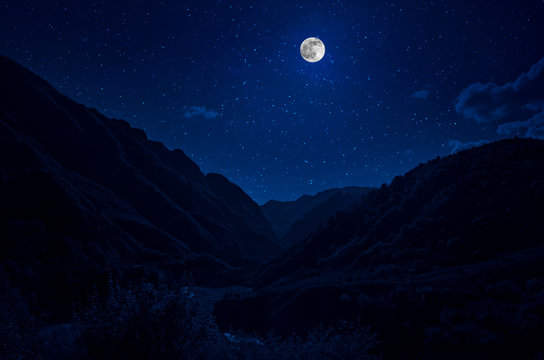 Mountain Road through the forest on a full moon night. Scenic night landscape of dark blue sky with moon. Azerbaijan