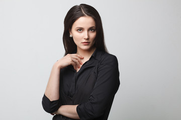 young brunette woman in elegant pose isolated on studio gray background