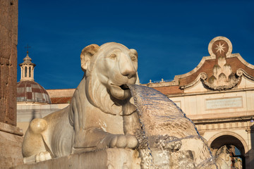 Marble egyptian lion from People Square central fountain with city wall ancient gate, in the background, in the center of Rome (erected in 1823)