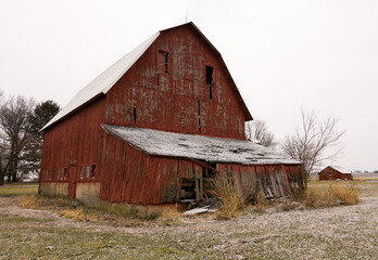 Old red barn in the rural countryside after a morning snow dusting.  Norway, Illinois, USA
