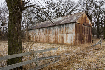 Old rusted metal building in open field.