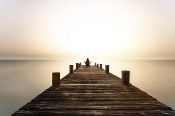 Person meditiert bei Sonnenuntergang auf einem Steg am Meer