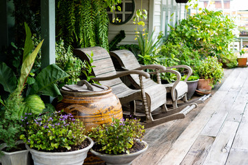 Wooden rocking chairs in a cottage garden porch setting on wooden floor in vintage Thai botanical garden, with traditional Thai old water jar decoration. Wall mural