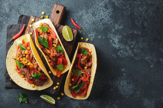 Mexican tacos with beef, vegetables and salsa. Tacos al pastor on wooden board on black background. Top view with copy space