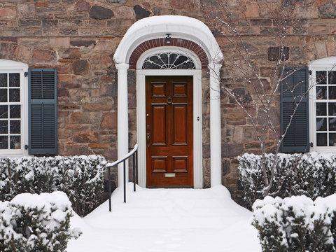 elegant wooden front door of house in winter, steps covered in snow