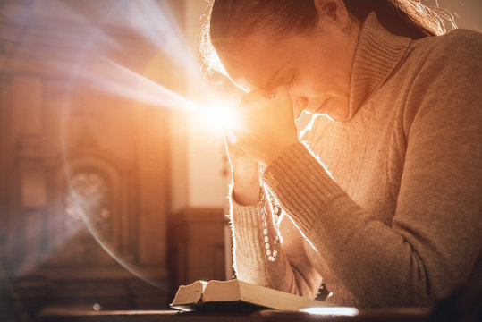 Christian woman praying in church. Hands crossed and Holy Bible on wooden desk.