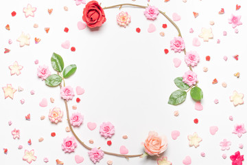 Frame made of rose flowers on white background. Top view with copy space.