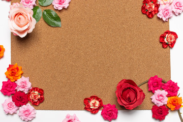 Frame made of rose flowers on cork board  background. Top view with copy space.