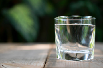 Drinking water in the glass on on the wooden table with green tropical tree at the background.