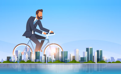 businessman riding bicycle office worker cycling healthy lifestyle concept business man over big modern city building skyscraper cityscape skyline flat horizontal