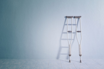 Success concept with crutches in the shadow of ladder.