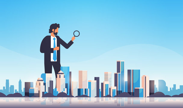 businessman holding magnifying glass search concept over big modern city building skyscraper cityscape skyline flat horizontal