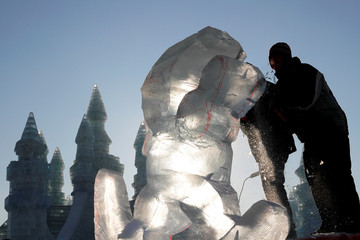 Artists carve ice sculptures during the sculpture contest as part of annual ice festival in Harbin