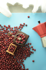 fresh coffee beans in grinder and red kettle on the side on blue background