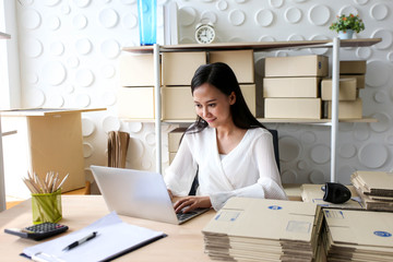 Young asian girl is freelancer Start up small business owner writing address on cardboard box at...