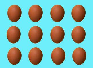 Pattern of brown chicken eggs isolated on blue pastel background. Top view. Minimalistic design