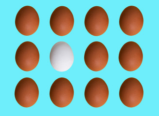 Pattern of brown white chicken eggs isolated on blue pastel background. Top view. Minimalistic design