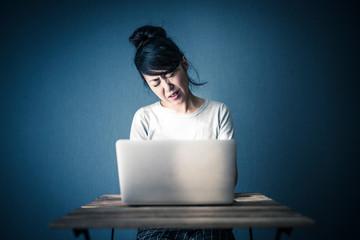 パソコンをみて困る女性