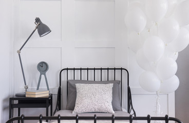 Bunch of white balloons next to single black metal bed with grey bedding and patterned pillow, real photo with copy space on the empty wall