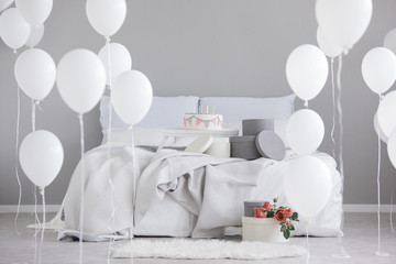 Birthday cake with candles in the middle of king size bed with grey bedding, real photo with copy space on the empty wall