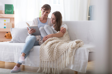 Caregiver reading book to girl with blanket while relaxing at home