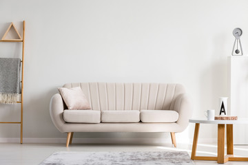Pillow on white sofa next to wooden coffee table with mugs, copy space on empty wall