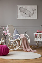 Pink pouf and flowers in grey baby's bedroom interior with poster and rocking chair. Real photo