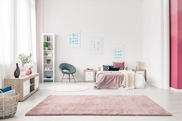 Stylish open plan bedroom interior with pastel pink design with king size bed and fluffy rug