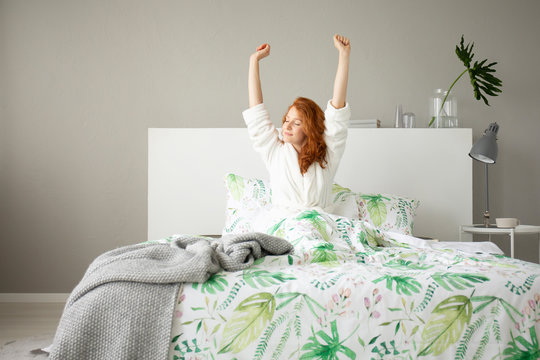 Smiling redhead girl waking up in big comfortable bed with floral bedding and grey blanket, real photo of grey bedroom design