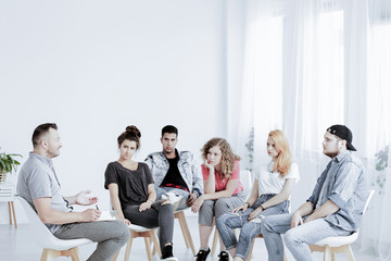 Group of teenagers during psychotherapy with professional counselor , copy space on empty white wall