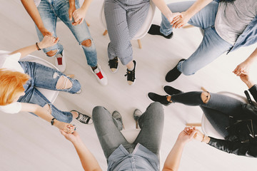 Top view of group of people holding hands during psychotherapy session