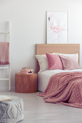 Pink pillows and blanket on white bedding in fashionable girl's bedroom interior