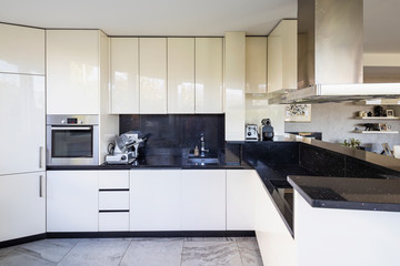 White kitchen with black marble top and large hood