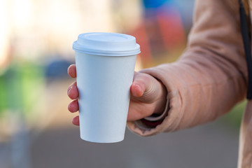 Young woman in casual clothes holding paper coffee cup and enjoying the walk in the city in the morning on a sunny day. Coffee away and to go
