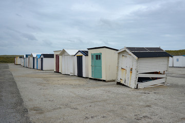 Row of multiple old discarded and damaged beach sheds on the beach of island Texel in the Netherlands