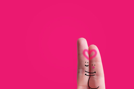 Gender reveal pregnancy announcement concept: two fingers with faces representing a couple with a pregnant woman hugging each other on a pink background - it is a girl