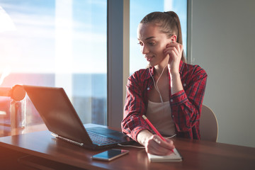 Student using online education service. Young woman looking in laptop display watching training foreign language courses and listening it with headphones. Modern study technology concept.