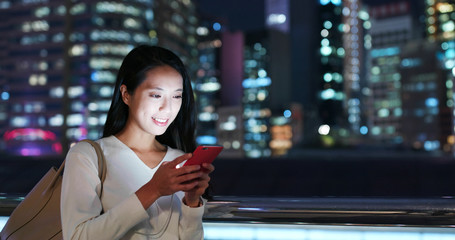 Wall Mural - Woman work on smart phone in city over business tower background