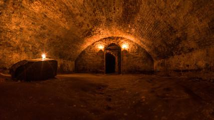 Scottish underground dungeon halls lit only by torchlight