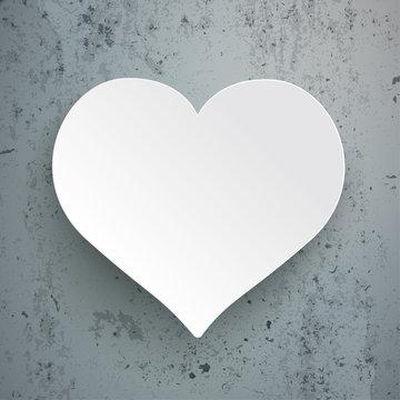 Weißes Herz aus Papier auf Sichtbeton