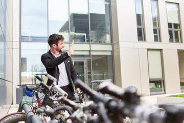 Business Mann vor dem Büro am Fahrradstand