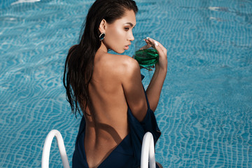 girl in a blue evening dress with a glass stands in the pool