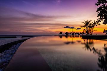 Reflektionen eines romantischen Sonnenunterganges im Pool auf einer tropischen Insel auf den Malediven