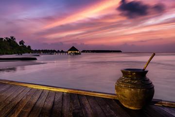 Sonnenuntergang über einer tropischen Insel auf den Malediven mit Holzsteg und Keramikvase
