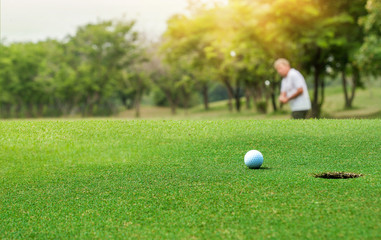 Golf ball near the hole on blurred Professional golfer shot Golf ball after sand blasting the bunker shot in golf course at Thailand.