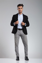 handsome smart casual man in black suit standing