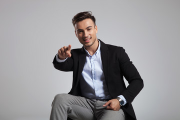 portrait of handsome businessman pointing finger while sitting