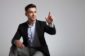 seated casual man pointing finger up looks to side