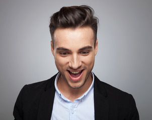 portrait of surprised casual man looking down with mouth open